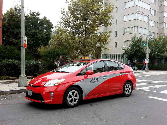 Image of a red taxicab with a silver accent on a D.C. street corner