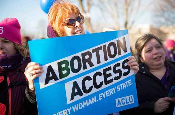 """Image description: an image of a light-skinned person with red hair at a protest, holding a blue sign that states """"ABORTION ACCESS: every woman, every state"""" with an ACLU logo in the bottom right corner of the sign"""