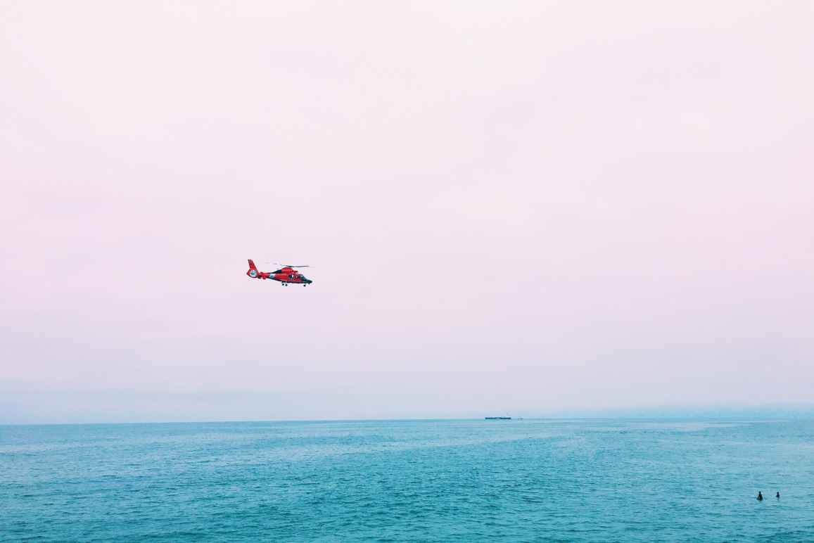Image description: a long shot of a red helicopter above turquoise waters. Two surfers appear as small dots in the lower right corner of the frame. The background horizon is a light pastel pink.
