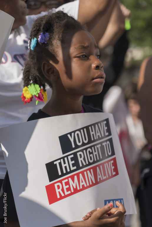 """young girl holding sign that reads """"you have the right to remain alive"""""""