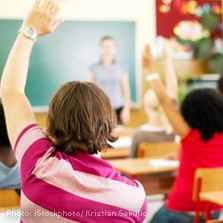 Light-skinned child raising their hand in a classroom setting with other students and a teacher in the background