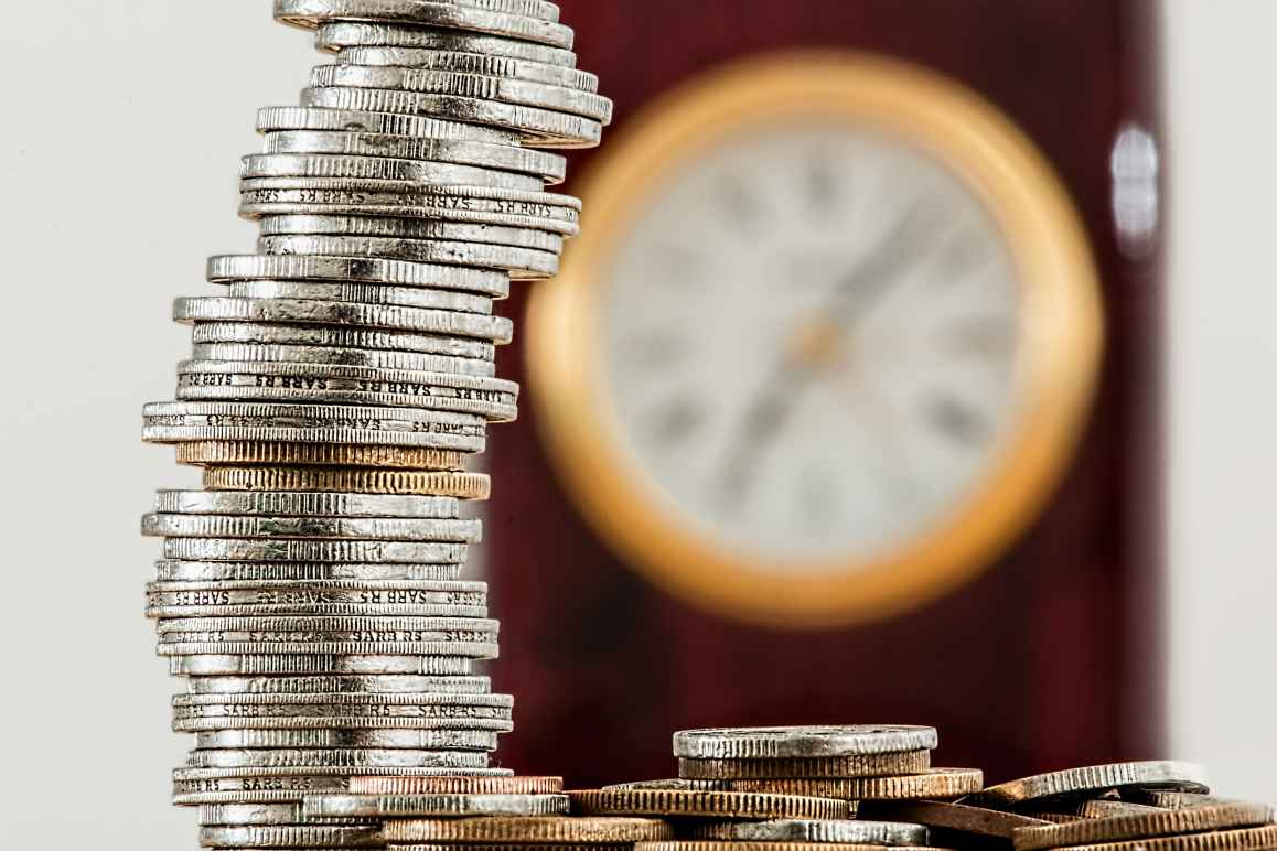 stack of coins with clock in background to illustrate a budget