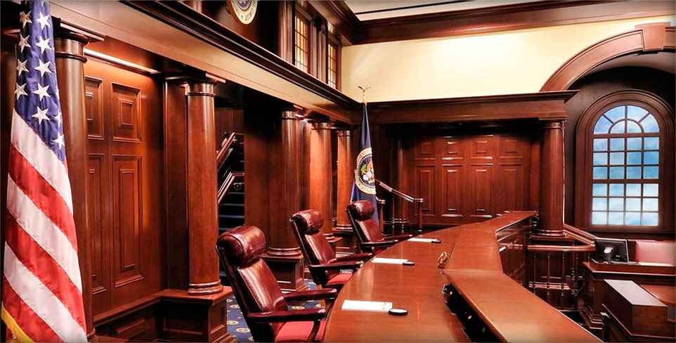 ID: the judges' bench in a courtroom in the Court of Appeals for the Federal Circuit. Three seats face to the right and the judges' bench extends outwards into the background. Mahogany paneling glows from the light overhead.