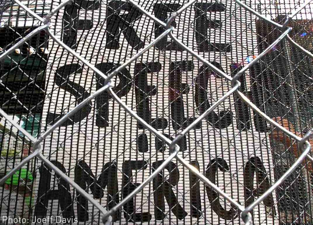 "Image description: a sign stating ""Free speech in America"" behind a chainlink fence."