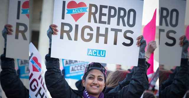 """Smiling person holding an """"I heart Repro Rights"""" sign"""