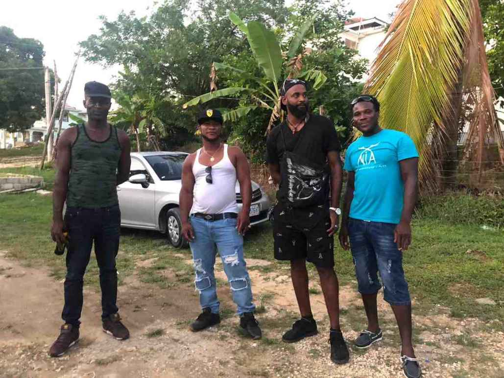 Image description: Plaintiffs Robert Dexter Weir, Patrick Wayne Ferguson, David Roderick Williams, and Luther Fian Patterson are next to each other. They are surrounded by lush jungle greenery and stand in front of a white car.