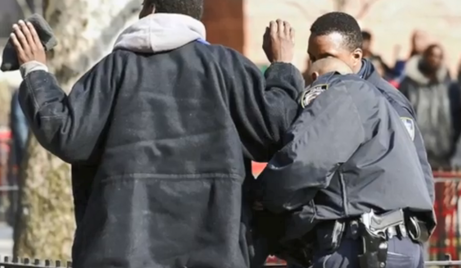 Image description: image of a person of color with his hands up and getting searched by a police officer