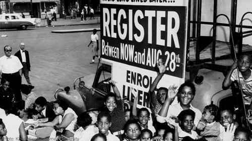 Image from the 1960's of African American youth smiling and gesturing in front of a sign that encourages black voters to register