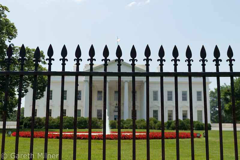 photo of white house through fence