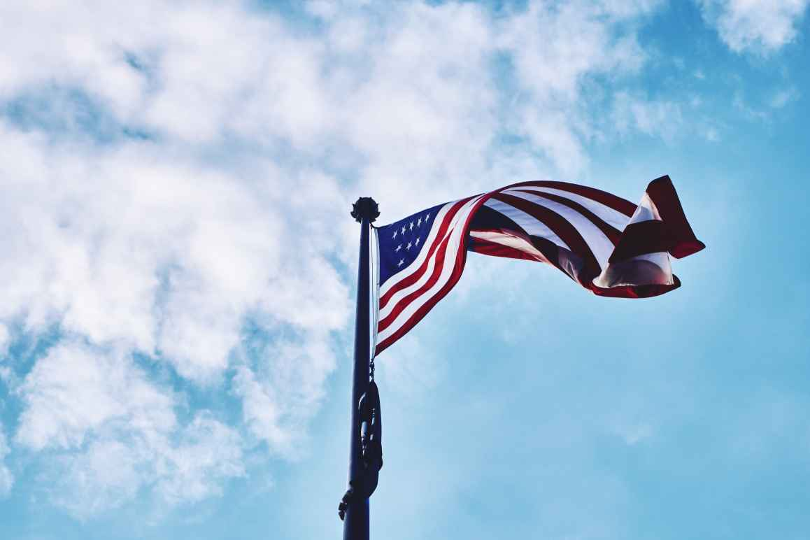 American flag waving with blue sky and light clouds in the background