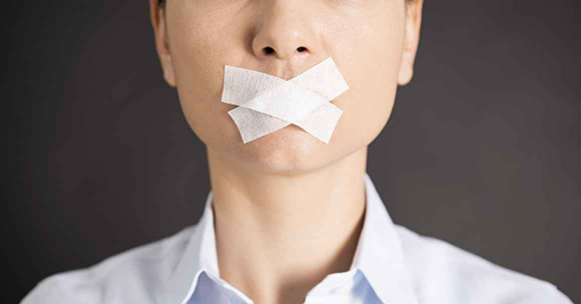 professional woman with tape over mouth indicated censorship